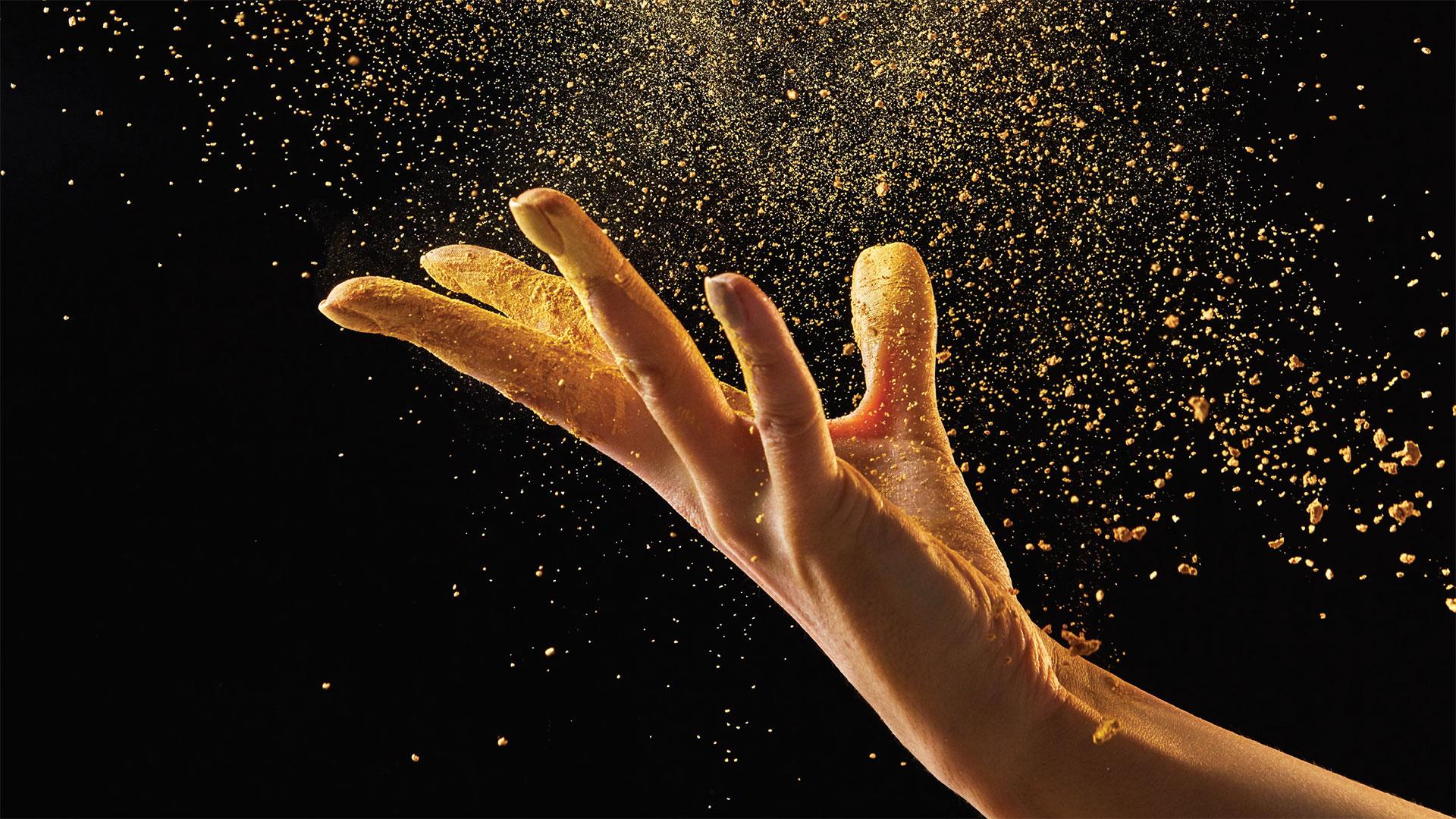 hand met goud stof